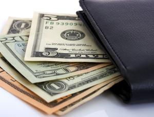 Several Dollar Bills Tucked In A Wallet